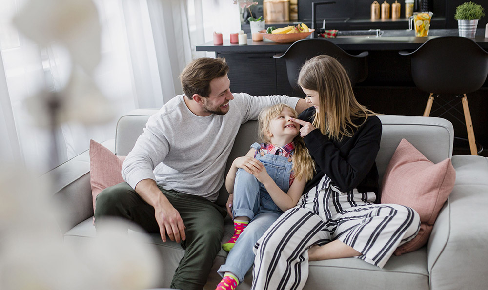 Glückliche Familie auf Sofa in Eigenheim